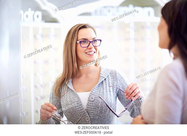 Optician counseling woman in shop