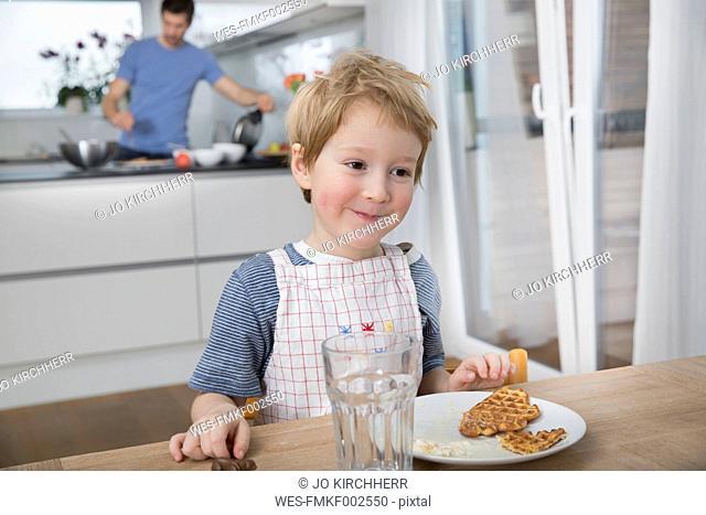Little boy eating waffles in kitchen