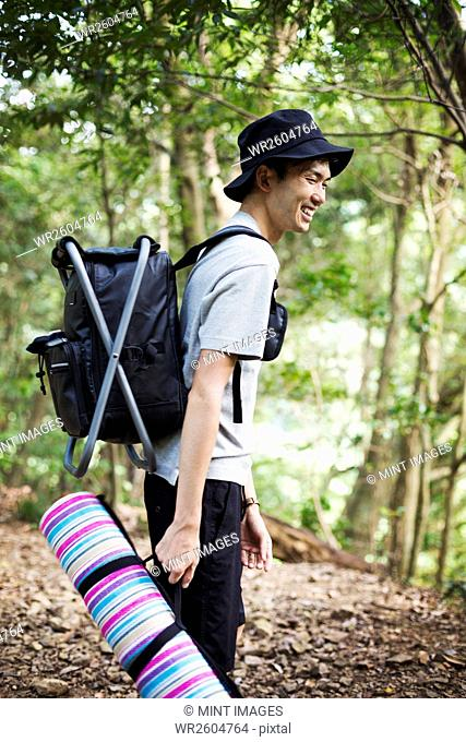 Man standing in a forest, carrying a picnic rug and backpack