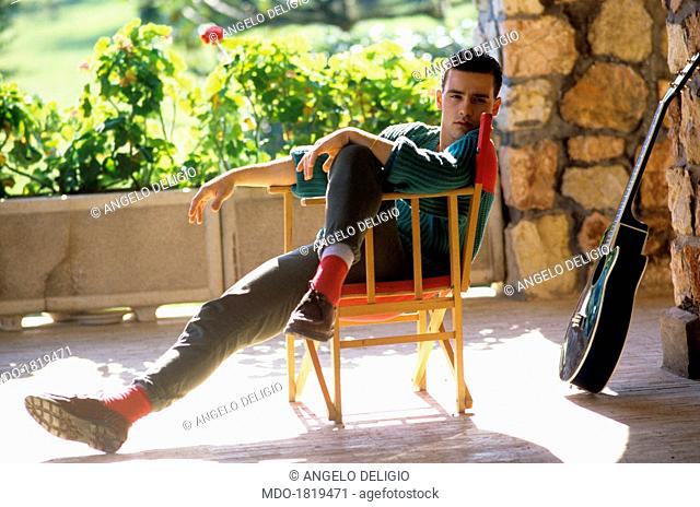 Italian singer-songwriter Eros Ramazzotti sitting on a folding chair and looking into the camera. Italy, 1986