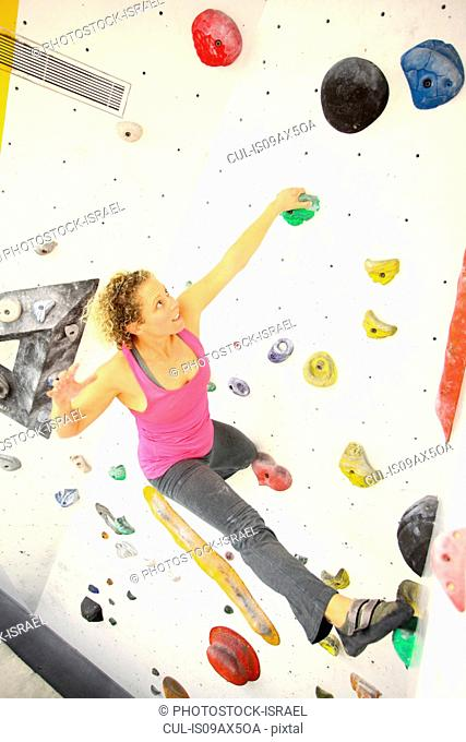 Woman climbing indoor artificial climbing wall