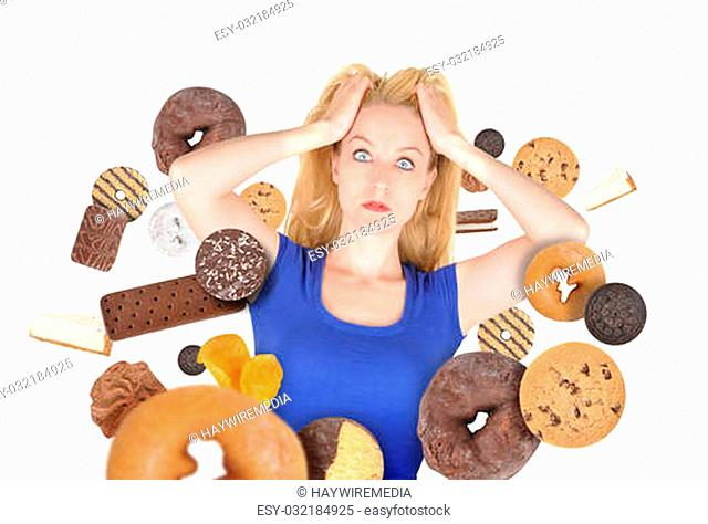 A woman has sweet food snacks around her on a white background. She has fear and there are donuts and cookies