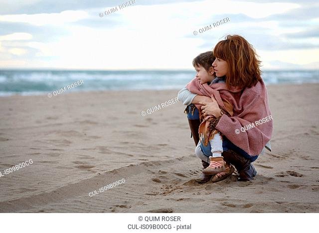 Mother and daughter wrapped in blanket hugging on beach