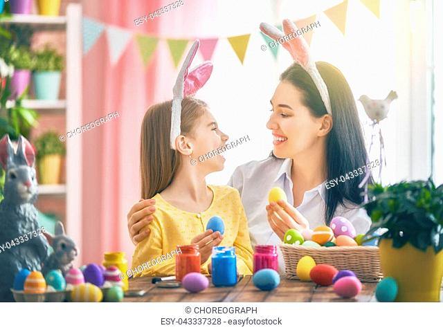 Happy holiday! A mother and her daughter are painting eggs. Family preparing for Easter. Cute little child girl is wearing bunny ears