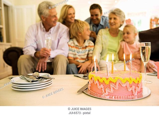 Three generation family sitting on sofa at home, birthday cake on coffee table in foreground