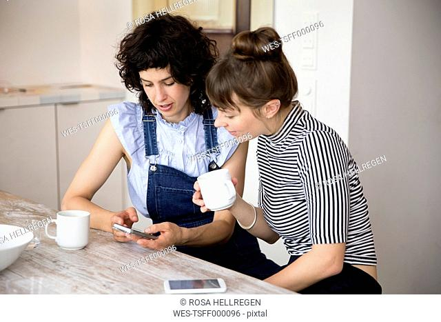 Two friends sitting in the kitchen looking together at smartphone