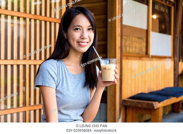 Woman drinking with iced coffee in coffee shop
