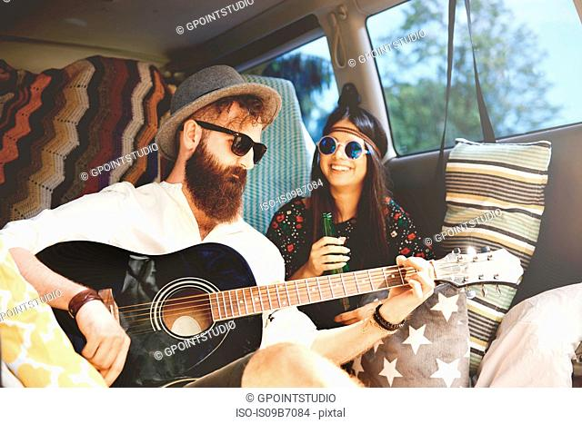 Young boho couple playing acoustic guitar in recreational van