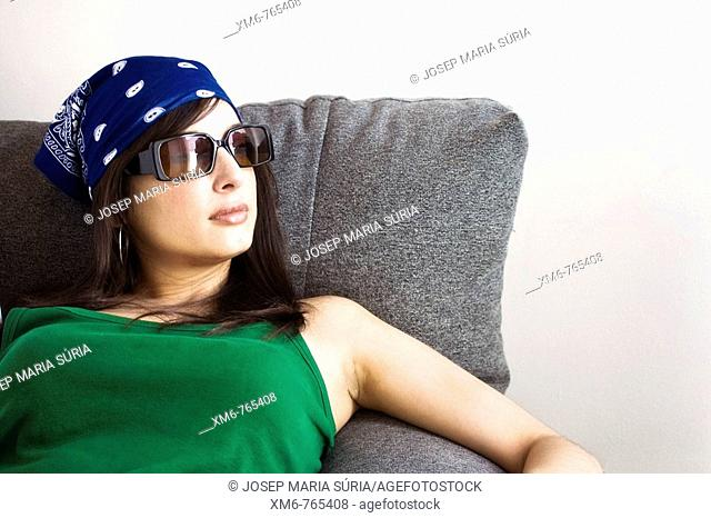 Girl sitting on the couch by the window looking pensive