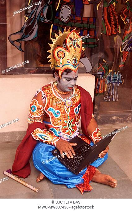 A South Indian dancer works with his laptop before a stage show at a dance festival in Kolkata January 24, 2004 These dancers came from a remote village of...