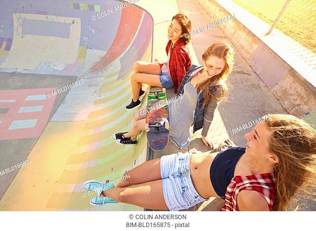 Friends sitting on ramp in skate park