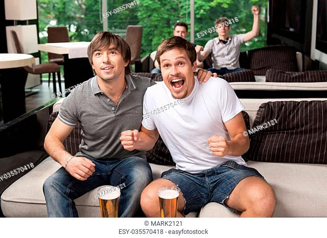 Group of fans cheering football team in beer pub. Having happy emotions on face