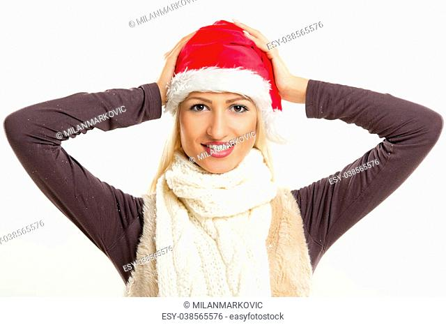 A young pretty blonde girl with a Santa's cap smiling looking at the camera while her hands puts a cap on her head
