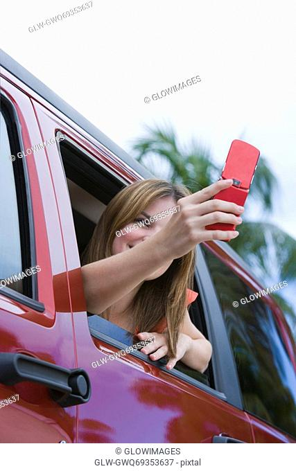Young woman sitting in a car and taking a picture with a mobile phone