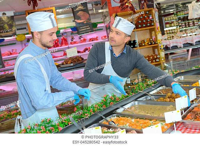 Man arranging trays of food in buffet counter