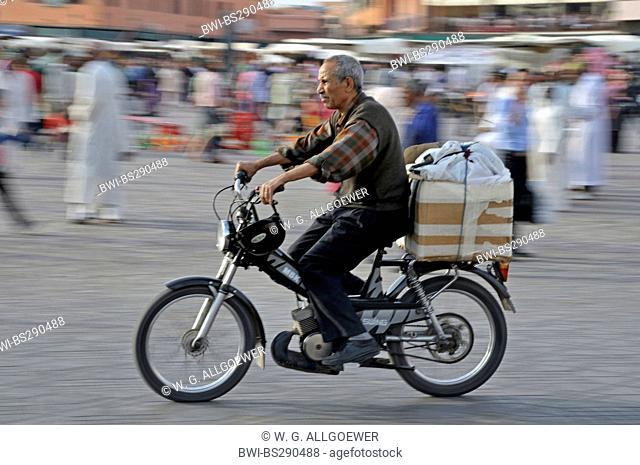 Moroccan on a moped crossing Djemaa El Fna , Morocco, Marrakesh, Medina, Djemaa El Fna