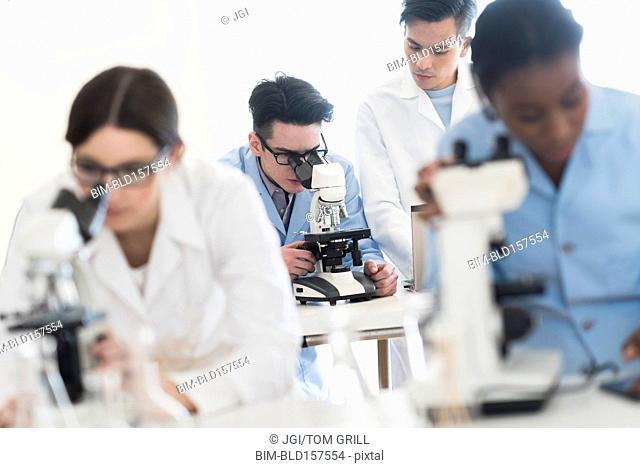 Scientists using microscopes in research laboratory