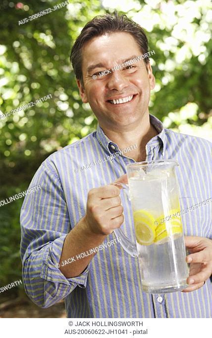 Portrait of a mature man holding a pitcher of lemonade