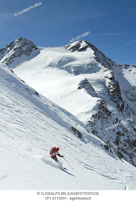 Freerider in descent, from a steep glacier, with peaks in the background. Santa Caterina Valfurva, Sondrio, Lombardy, Italy