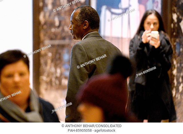 Former Republican presidential candidate Ben Carson waves to bystanders as he walks through the lobby of the Trump Tower in New York, New York
