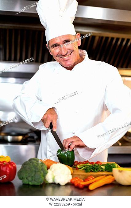Chef slicing vegetables on wooden board