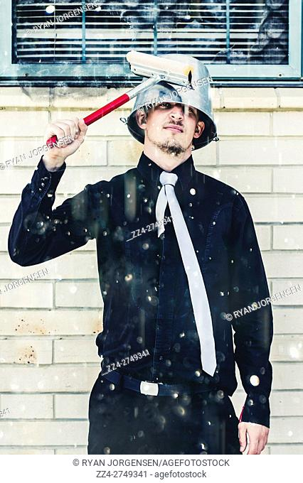 Humorous portrait of young cleaning man in elegant black clothes and tie with metal bucket on head holding squeegee in rain. Ready to clean