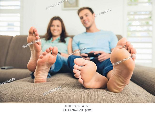 Couple barefoot on sofa using video game controller