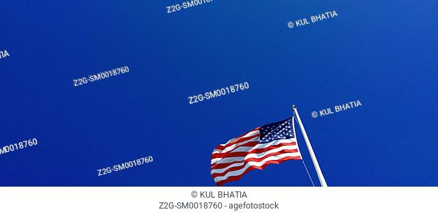 The American flag blows in the wind on a blue sky day, Pearl Harbour, Hawaii, USA