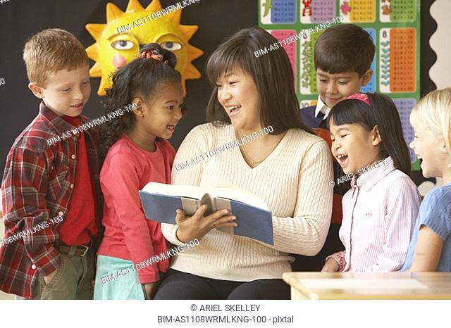 Asian female teacher reading to students