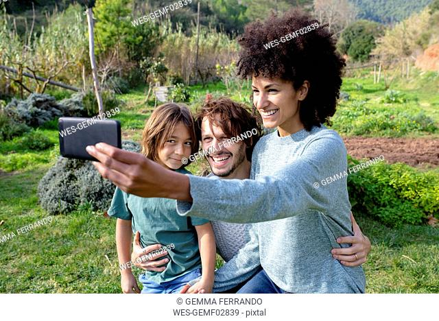 Happy family sitting on a bench in a garden, mother taking selfies