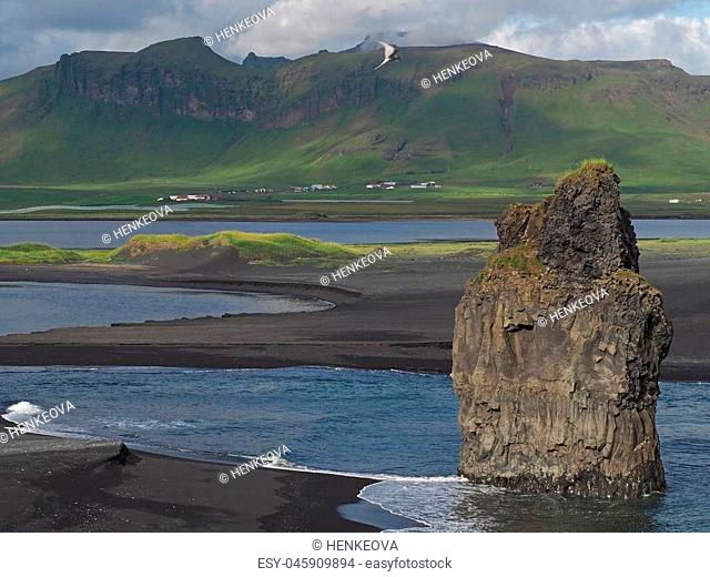 magic iceland landscape with black lava sand and green eroded hills