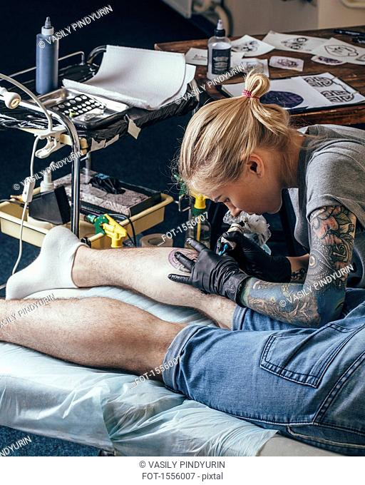 Artist tattooing design on man's leg at studio