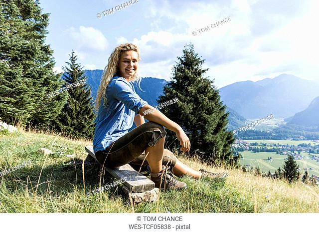 Germany, Bavaria, Oberammergau, portrait of smiling young woman sitting on bench on mountain meadow