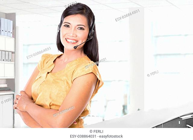 A portrait of an Asian woman using a headset, smiling at the camera