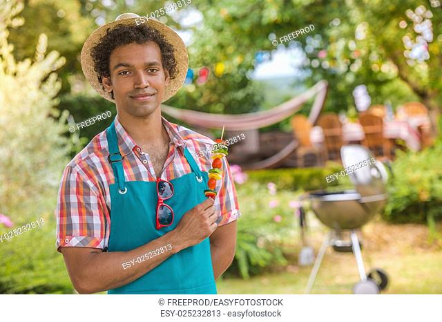 Handsome man preparing barbecue for friends, France