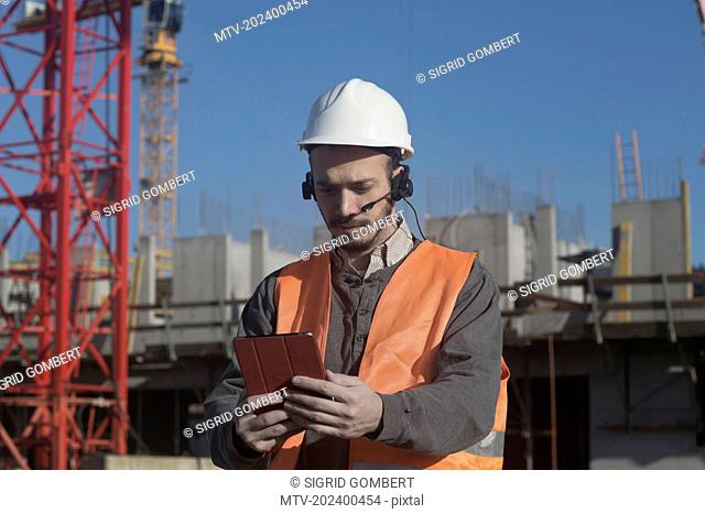 Young male engineer using digital tablet at construction site, Freiburg Im Breisgau, Baden-Württemberg, Germany