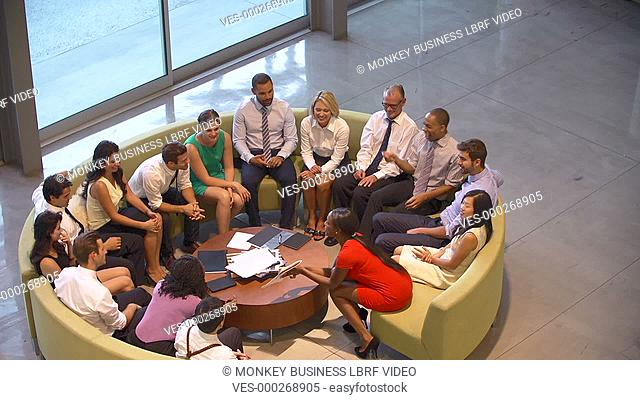 Overhead view of businesspeople giving one another high fives as part of team building exercise.Shot on Sony FS700 in PAL format at a frame rate of 25fps