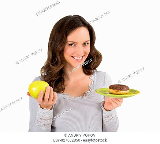 Young Happy Woman Holding Green Apple And Donut In Front Of Fridge