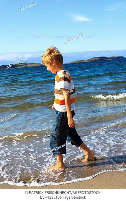 boy running on sandy beach, Sutherland, Scotland