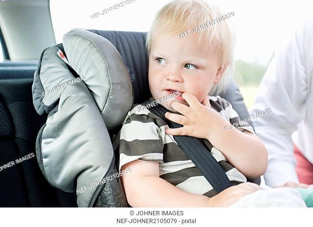 Baby boy sitting in car safety-seat