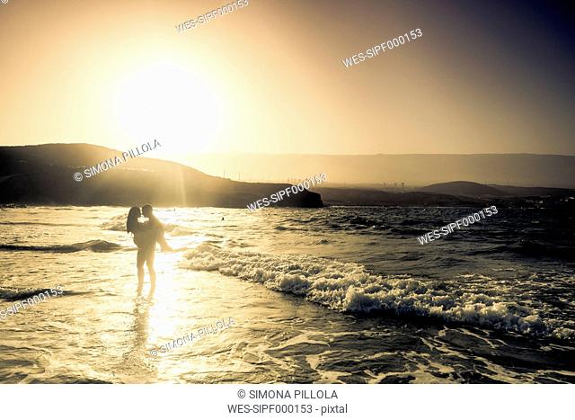 Spain, Tenerife, silhouette of young couple in love at seafront