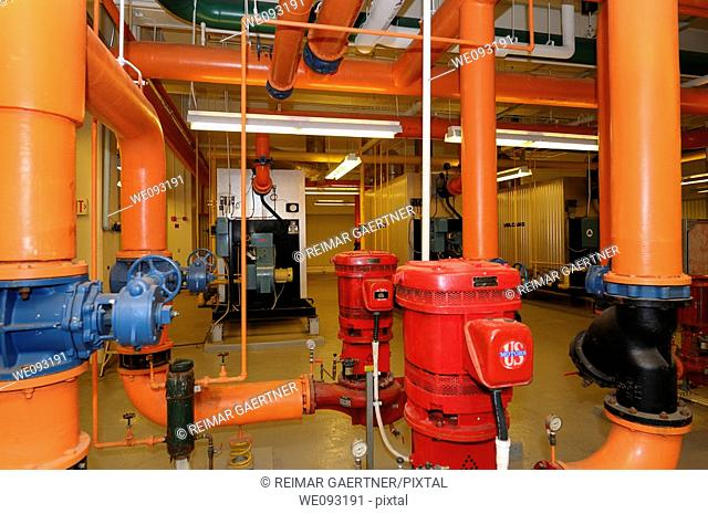 Row of furnaces and hot water pipes in the boiler room of a highrise office building
