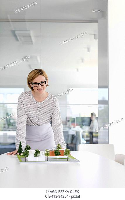 Portrait confident female architect with model in conference room