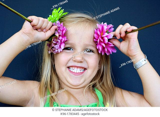 silly little girl playing with flowers