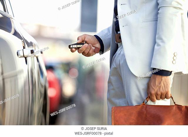 Businessman unlocking his car, close up