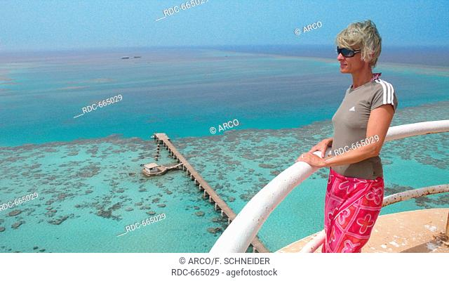 woman looking at red sea reef with jetty from Sanganeb lighthouse, Sudan, Africa