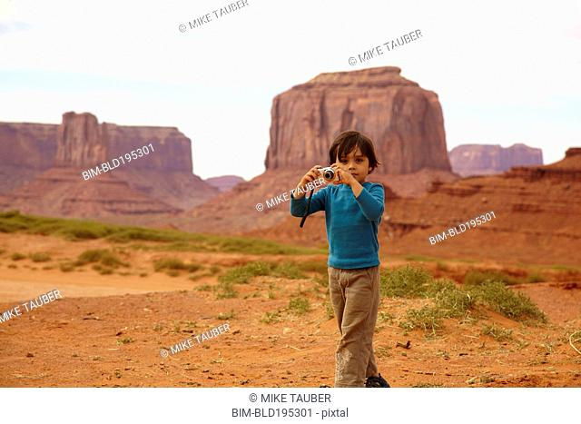 Mixed race boy taking pictures in Monument Valley