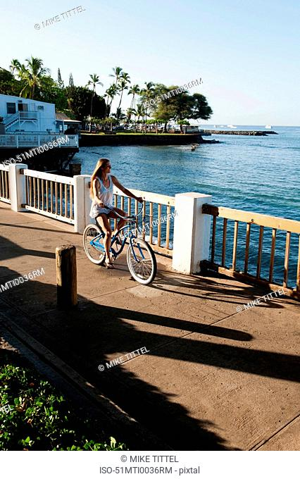 Woman riding bicycle on waterfront