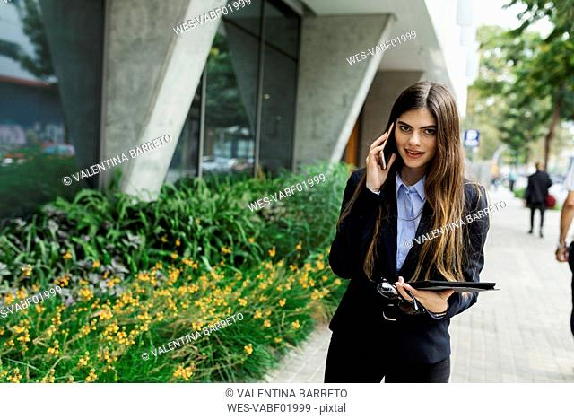 Portrait of smiling young businesswoman on cell phone in the city
