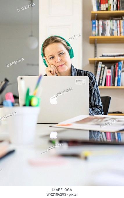 Thoughtful mature businesswoman wearing headphones in office